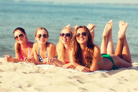 zomer vakantie, vakanties, reizen en mensen concept - groep van lachende jonge vrouwen in zonnebril liggend op het strand
