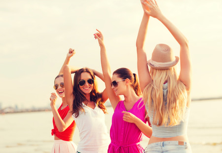niña: las vacaciones de verano, las vacaciones, los viajes y el concepto de la gente - grupo de mujeres jóvenes sonrientes en gafas de sol y ropa casual bailando en la playa