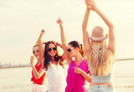 mädchen: Sommerferien, Urlaub, Reisen und Menschen Konzept - Gruppe von lächelnde junge Frauen mit Sonnenbrille und Freizeitkleidung tanzen am Strand