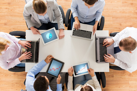 business, people and technology concept - close up of creative team with laptop and tablet pc computers displaying charts on screens sitting at table in office