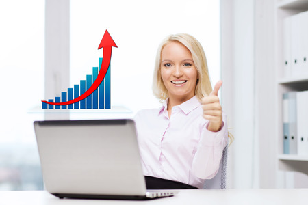 thumbsup: business, success, people, gesture and technology concept - smiling businesswoman showing thumbs up with laptop computer and growing chart in office