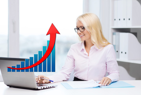 the bookkeeper: business, people, statistics and technology concept - smiling businesswoman with laptop computer, papers and growing chart sitting in office Stock Photo