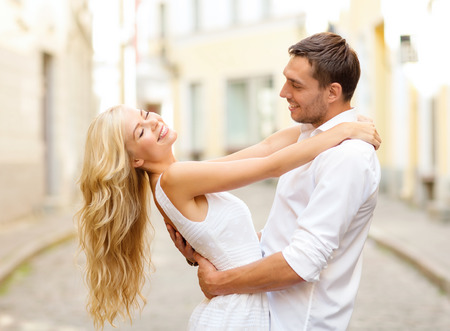 summer holidays, love, relationship and dating concept - smiling couple dancing in the city Foto de archivo