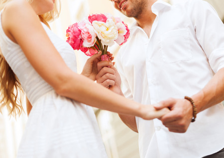 dating: summer holidays, love, relationship and dating concept - couple with bouquet of flowers in the city
