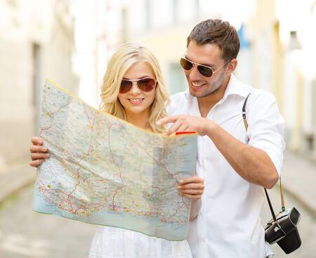 luna de miel: días de fiesta, de citas y de concepto de turismo de verano - par sonriente en gafas de sol con el mapa de la ciudad Foto de archivo