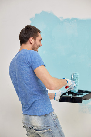 repair, building, people and renovation concept - happy man with roller painting wall in blue at home