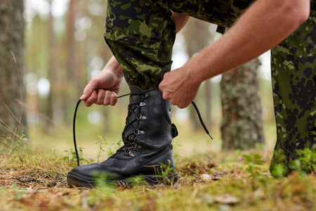 infantryman: war, hiking, army and people concept - close up of soldier boots and hands tying bootlaces in forest