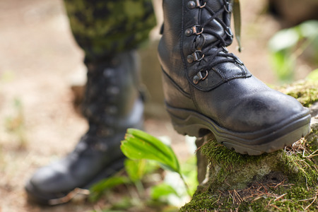 military boots: war, hiking, army and people concept - close up of soldier feet in army boots in forest