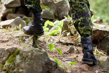 infantryman: war, hiking, army and people concept - close up of soldier legs climbing on rocks in forest Stock Photo