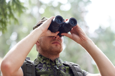 army face: hunting, war, army and people concept - young soldier, ranger or hunter with binocular observing forest