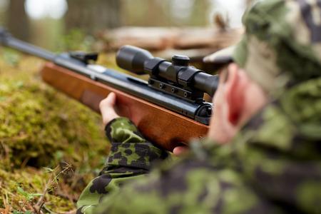 cazador: la caza, la guerra, el ejército y la gente concepto - joven soldado, guardabosques o cazador con arma caminando en el bosque