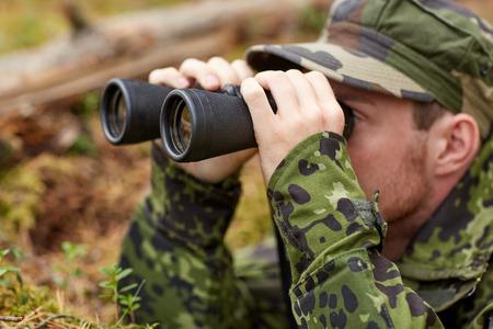 soldado: la caza, la guerra, el ejército y la gente concepto - joven soldado, guardabosques o cazador con bosque observación binocular Foto de archivo