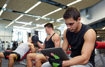 sport, bodybuilding, lifestyle, technology and people concept - group of men with tablet pc computer flexing muscles in gym