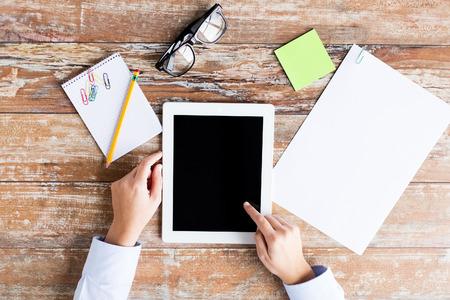 bedrijfsleven, onderwijs, mensen en technologie concept - close-up van vrouwelijke handen wijzende vinger naar tablet-pc computer zwart leeg scherm met papier, notebook en brillen