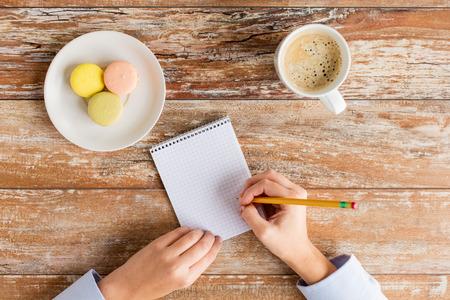 het bedrijfsleven, het onderwijs en de mensen concept - close-up van vrouwelijke handen met met notebook, potlood, koffie en koekjes op tafel