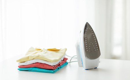 laundry pile: ironing, clothes, housework and objects concept - close up of iron and clothes on table at home
