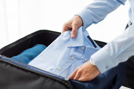 business, trip, luggage and people concept - close up of businessman packing clothes into travel bag Stockfoto