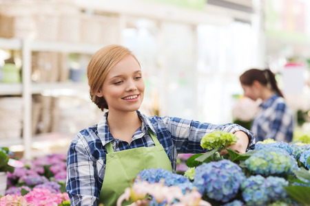 人、ガーデニング、職業の概念 - 幸せな女や庭師の温室で花の世話