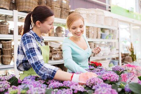 consumerism: people, gardening, shopping, sale and consumerism concept - happy gardener helping woman with choosing flowers in greenhouse Stock Photo