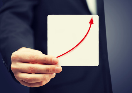 man in suit holding card with increasing graph on it photo