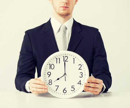 timezone: close up of man holding wall clock