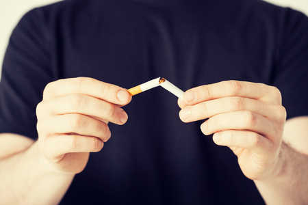 disallowed: close up of man breaking the cigarette with hands