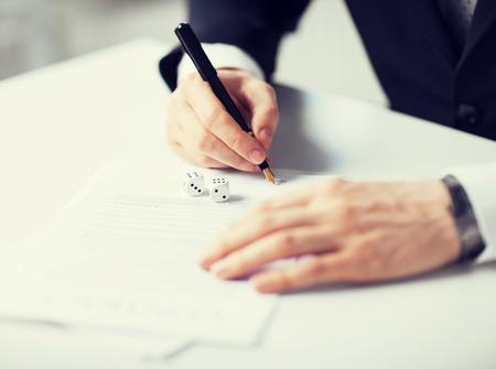 beeld van de man handen met gokken dobbelstenen ondertekening contract Stockfoto