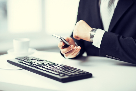 e marketing: man hands with keyboard watching time and holding smartphone