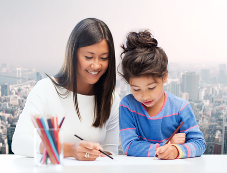 asian art: family, children, creativity and happy people concept - happy mother and daughter drawing with pencils over city background