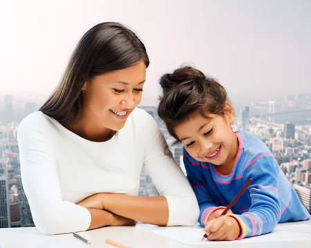 asian school girl: family, children, creativity and happy people concept - happy mother and daughter drawing with pencils over city background