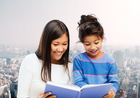 asian preteen: family, children, education and happy people concept - happy mother and little daughter reading book over city background