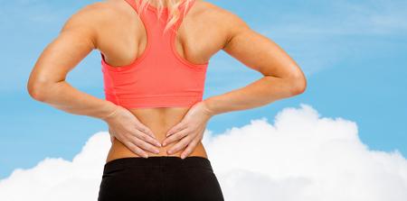 mujer deportista: fitness, salud y la medicina concepto - cerca de la mujer deportiva tocando su espalda Foto de archivo