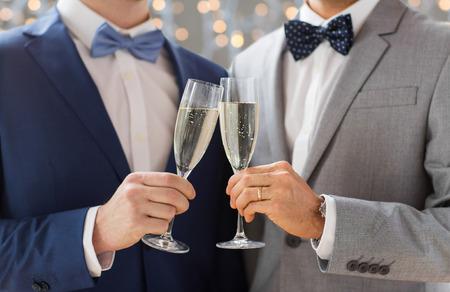 sex: mensen, viering, homoseksualiteit, het huwelijk en de liefde van hetzelfde geslacht concept - close-up van gelukkig getrouwd mannelijk homopaar het drinken van mousserende wijn op de bruiloft op vakantie steekt achtergrond aan Stockfoto