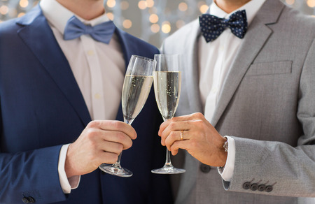 same sex: people, celebration, homosexuality, same-sex marriage and love concept - close up of happy married male gay couple drinking sparkling wine on wedding over holidays lights background