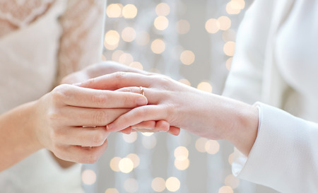 people, homosexuality, same-sex marriage and love concept - close up of happy lesbian couple hands putting on wedding ring over holidays lights background 스톡 콘텐츠