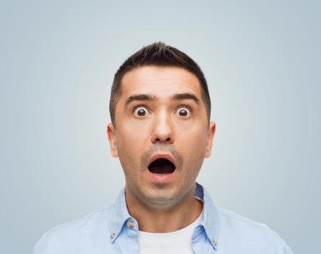 Angst, Emotionen, Horror und Menschen Konzept - Angst Mann mit großen Augen und offenem Mund schreiend über grauem Hintergrund
