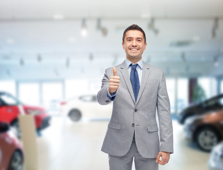 Negócios automotivos, venda de automóveis, consumo, gesto e conceito de pessoas - homem feliz mostrando polegares acima do show de auto ou salão de beleza