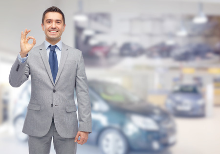 business, car sale, consumerism and people concept - happy man over auto show or salon background Stock Photo
