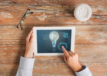 business, people, progress and technology concept - close up of hands pointing finger to tablet pc computer screen with lighting bulb, coffee cup and eyeglasses on table photo
