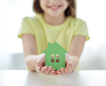 people, charity, family and home concept - close up of happy girl holding green paper house cutout in cupped hands