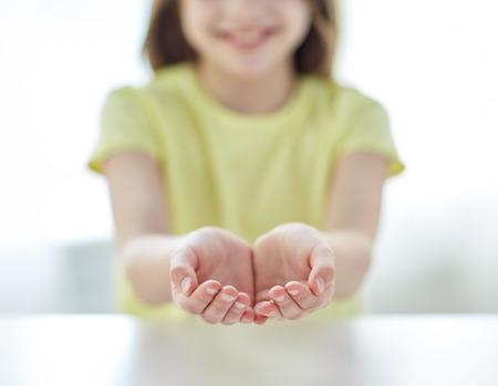 mensen, liefdadigheid, jeugd en reclame concept - close-up van kind holle handen thuis Stockfoto