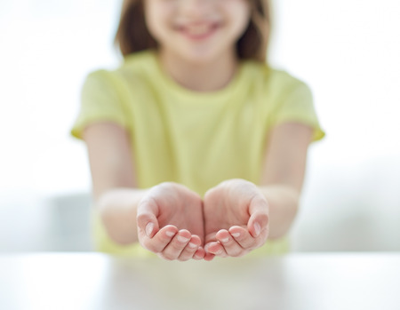 people, charity, childhood and advertisement concept - close up of child cupped hands at home Stock fotó
