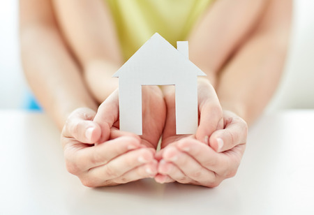 hands cupped: people, charity, family and home concept - close up of woman and girl holding paper house cutout in cupped hands Stock Photo