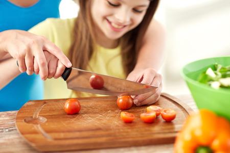 cereza: comida, familia, cocinar y concepto de la gente - cerca de la chica feliz y madre haciendo la cena y picar los tomates cereza en la tabla de cortar con un cuchillo en la cocina