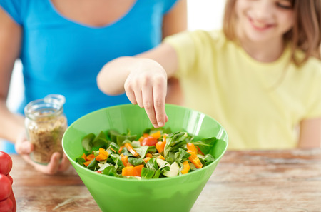 food, healthy eating, family and people concept - close up of happy girl and mother cooking salad for dinner and adding spices in kitchen