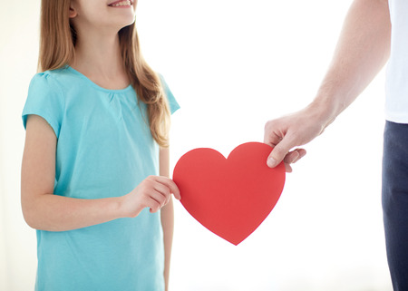 people, love, charity and family concept - close up of girl and male hand holding red heart shape at home photo
