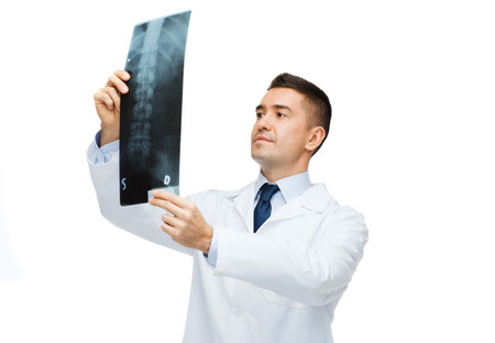 healthcare, rontgen, people and medicine concept - male doctor in white coat looking at x-ray photo