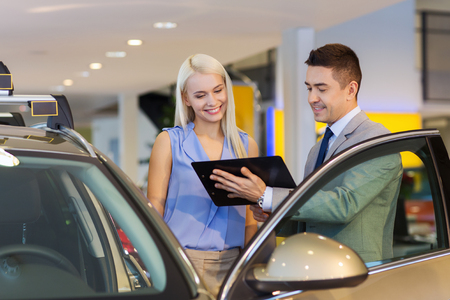 auto sales: auto business, car sale, consumerism and people concept - happy woman with car dealer in auto show or salon Stock Photo
