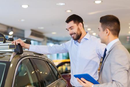 negocio de autos, venta de los vehículos, la tecnología y el concepto de la gente - hombre feliz y distribuidor de coche con el ordenador Tablet PC en la demostración auto o salón