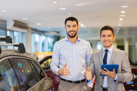 auto business, car sale, technology, gesture and people concept - happy man and car dealer with tablet pc computer showing thumbs up in auto show or salon